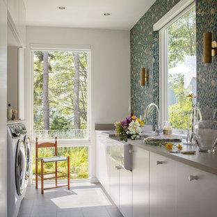 Foto di una sala lavanderia con lavello stile country, ante lisce, ante bianche, pareti grigie, lavatrice e asciugatrice affiancate, pavimento grigio, top grigio e carta da parati