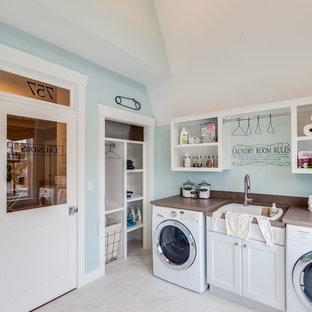 Foto di una lavanderia multiuso stile marinaro con lavello da incasso, ante in stile shaker, ante bianche, top in legno, pareti blu, lavatrice e asciugatrice affiancate e top marrone