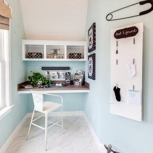 Inspiration for a large nautical single-wall utility room in Other with a built-in sink, recessed-panel cabinets, white cabinets, laminate countertops, blue walls, marble flooring and a side by side washer and dryer.