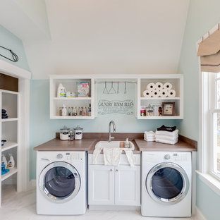 This is an example of a large coastal utility room in Other with a built-in sink, recessed-panel cabinets, white cabinets, laminate countertops, blue walls, marble flooring and a side by side washer and dryer.