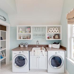 Foto di una grande lavanderia multiuso stile marinaro con lavello da incasso, ante con riquadro incassato, ante bianche, top in laminato, pareti blu, pavimento in marmo e lavatrice e asciugatrice affiancate