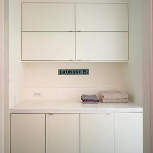 Cette image montre une petite buanderie linéaire minimaliste avec un placard à porte plane, des portes de placard beiges, un plan de travail en surface solide, un mur beige et des machines côte à côte.