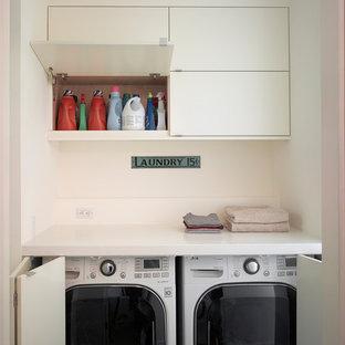 Ispirazione per un piccolo ripostiglio-lavanderia minimalista con ante lisce, top in superficie solida, pareti beige, ante bianche e lavatrice e asciugatrice nascoste
