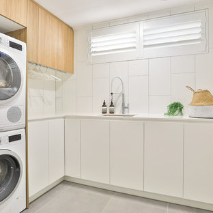 Photo of a contemporary l-shaped dedicated laundry room in Sydney with an undermount sink, flat-panel cabinets, white cabinets, quartz benchtops, white walls, ceramic floors, a stacked washer and dryer, grey floor and white benchtop.