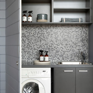 Inspiration for a small contemporary single-wall dedicated laundry room in Melbourne with a single-bowl sink, flat-panel cabinets, grey cabinets, quartz benchtops, grey walls, medium hardwood floors, a concealed washer and dryer, brown floor and grey benchtop.