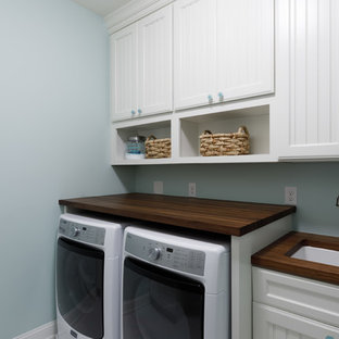 Photo of a mid-sized traditional dedicated laundry room in Other with white cabinets, blue splashback, glass tile splashback, light hardwood floors, a farmhouse sink, wood benchtops, grey walls, a side-by-side washer and dryer, brown benchtop and recessed-panel cabinets.