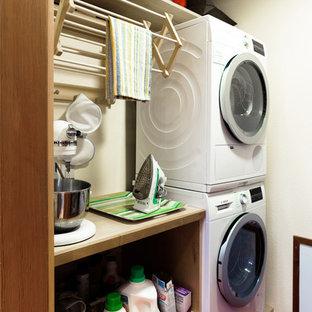 シアトルの小さいカントリー風おしゃれな家事室 (フラットパネル扉のキャビネット、淡色木目調キャビネット、木材カウンター、リノリウムの床、上下配置の洗濯機・乾燥機、赤い床、白い壁) の写真