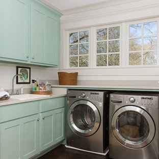 Inspiration for a mid-sized transitional l-shaped brown floor and dark wood floor dedicated laundry room remodel in Atlanta with blue cabinets, a drop-in sink, shaker cabinets, white walls, a side-by-side washer/dryer and beige countertops