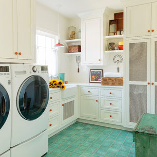 This is an example of a large country dedicated laundry room in Los Angeles with a farmhouse sink, shaker cabinets, white cabinets, quartz benchtops, white walls, ceramic floors, a side-by-side washer and dryer, green floor and white benchtop.