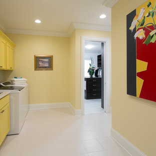 Photo of a large contemporary utility room in Cincinnati with a drop-in sink, yellow walls, ceramic floors and a side-by-side washer and dryer.