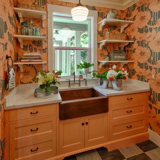 Idée de décoration pour une buanderie tradition de taille moyenne avec un évier de ferme, un placard à porte shaker, des portes de placard oranges, un plan de travail en quartz modifié, un sol en linoléum, des machines côte à côte, un mur multicolore et un plan de travail gris.