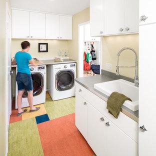 Idéer för en mellanstor retro l-formad tvättstuga enbart för tvätt, med en nedsänkt diskho, släta luckor, vita skåp, beige väggar, en tvättmaskin och torktumlare bredvid varandra och flerfärgat golv