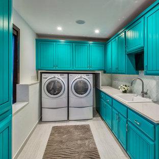 Esempio di una grande lavanderia multiuso boho chic con ante con bugna sagomata, ante blu, top in superficie solida, pareti bianche, lavatrice e asciugatrice affiancate, pavimento in laminato, pavimento grigio e lavello da incasso