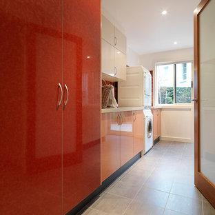 Aménagement d'une grande buanderie parallèle moderne dédiée avec un évier encastré, un placard à porte plane, un plan de travail en quartz modifié, un mur blanc, un sol en carrelage de porcelaine, des machines superposées et des portes de placard rouges.