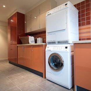 Exempel på en stor modern parallell tvättstuga enbart för tvätt, med en undermonterad diskho, släta luckor, orange skåp, bänkskiva i kvarts, vita väggar, klinkergolv i porslin och en tvättpelare