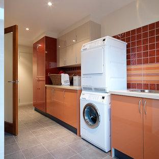 Idée de décoration pour une grande buanderie parallèle minimaliste dédiée avec un évier encastré, un placard à porte plane, des portes de placard oranges, un plan de travail en quartz modifié, un mur blanc, un sol en carrelage de porcelaine et des machines superposées.