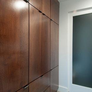 Idéer för en mellanstor modern parallell tvättstuga enbart för tvätt, med släta luckor, träbänkskiva, vita väggar, betonggolv, en tvättmaskin och torktumlare bredvid varandra och skåp i mörkt trä