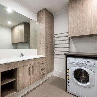 Неиссякаемый источник вдохновения для домашнего уюта: маленькая универсальная комната в стиле модернизм с фасадами с утопленной филенкой, светлыми деревянными фасадами, столешницей из ламината, белыми стенами, полом из керамогранита, с сушильной машиной на стиральной машине, коричневым полом и монолитной раковиной