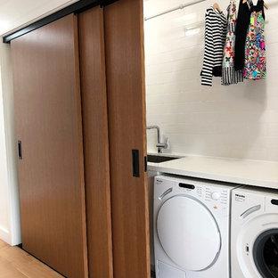 Bild på en liten funkis vita linjär vitt liten tvättstuga, med en undermonterad diskho, bänkskiva i kvarts, vita väggar, en tvättmaskin och torktumlare bredvid varandra, ljust trägolv och brunt golv