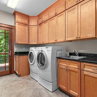 Esempio di una sala lavanderia stile americano di medie dimensioni con lavello da incasso, ante con riquadro incassato, ante in legno chiaro, top in granito, pareti beige, pavimento in gres porcellanato, lavatrice e asciugatrice affiancate, pavimento beige e top nero