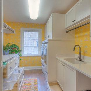 Idéer för en stor klassisk parallell tvättstuga enbart för tvätt, med gula väggar, klinkergolv i keramik, en undermonterad diskho, vita skåp, bänkskiva i kvarts, en tvättmaskin och torktumlare bredvid varandra och luckor med infälld panel
