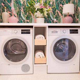 Immagine di una piccola sala lavanderia tropicale con ante bianche, top in superficie solida, pareti multicolore, pavimento con piastrelle in ceramica e lavatrice e asciugatrice nascoste
