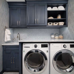 Zweizeilige, Kleine Klassische Waschküche mit blauen Schränken, Waschmaschine und Trockner nebeneinander, grauer Arbeitsplatte, Tapetenwänden, Einbauwaschbecken, Kassettenfronten, Marmor-Arbeitsplatte, bunter Rückwand, Rückwand aus Porzellanfliesen, blauer Wandfarbe, Marmorboden und weißem Boden in Sonstige