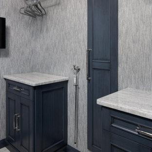Ispirazione per una piccola sala lavanderia classica con lavello da incasso, ante a filo, ante blu, top in marmo, paraspruzzi multicolore, paraspruzzi in gres porcellanato, pareti blu, pavimento in marmo, lavatrice e asciugatrice affiancate, pavimento bianco, top grigio e carta da parati