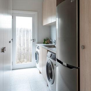 Idéer för att renovera en stor funkis vita linjär vitt tvättstuga enbart för tvätt, med släta luckor, skåp i ljust trä, bänkskiva i kvarts, grönt stänkskydd, stänkskydd i mosaik, vita väggar och en tvättmaskin och torktumlare bredvid varandra