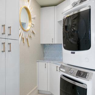 Cette photo montre une buanderie parallèle tendance avec un placard à porte plane, des portes de placard blanches, un mur beige, des machines superposées, un sol beige et un plan de travail bleu.