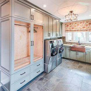 Idéer för att renovera en stor vintage vita u-formad vitt tvättstuga enbart för tvätt, med en rustik diskho, luckor med infälld panel, gröna skåp, bänkskiva i kvartsit, vita väggar, skiffergolv, en tvättmaskin och torktumlare bredvid varandra och grått golv