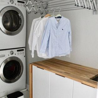 Esempio di una piccola sala lavanderia minimalista con lavello sottopiano, ante lisce, ante bianche, top in legno, pareti bianche, pavimento con piastrelle in ceramica, lavatrice e asciugatrice a colonna, pavimento grigio e top arancione