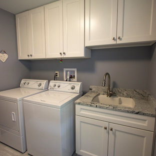 This is an example of a medium sized traditional single-wall separated utility room in Cleveland with an utility sink, recessed-panel cabinets, white cabinets, granite worktops, blue walls, ceramic flooring, a side by side washer and dryer and grey floors.