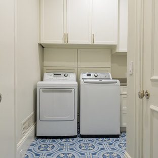 This is an example of a large classic l-shaped separated utility room in Dallas with a submerged sink, recessed-panel cabinets, white cabinets, engineered stone countertops, white walls, ceramic flooring, a side by side washer and dryer, blue floors and grey worktops.