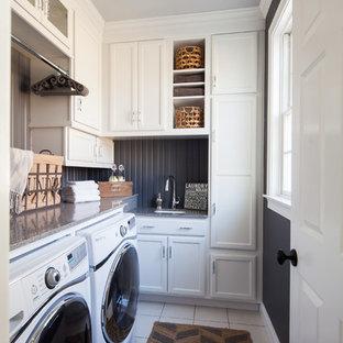 Immagine di una piccola sala lavanderia classica con lavello sottopiano, ante con riquadro incassato, ante bianche, top in granito, pavimento con piastrelle in ceramica, lavatrice e asciugatrice affiancate e pareti nere