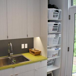 Idéer för mellanstora funkis gult tvättstugor enbart för tvätt, med en dubbel diskho, släta luckor, grå skåp, laminatbänkskiva, grå väggar, mellanmörkt trägolv, en tvättmaskin och torktumlare bredvid varandra och grått golv