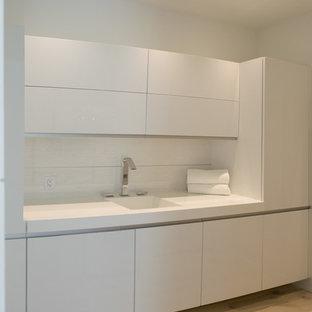 Inspiration pour une buanderie linéaire minimaliste dédiée et de taille moyenne avec un évier intégré, un placard à porte plane, des portes de placard blanches, un plan de travail en quartz modifié, un mur blanc, un sol en bois clair, des machines dissimulées et un sol beige.