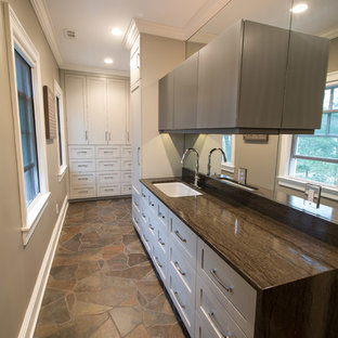 Large contemporary single-wall separated utility room in New York with a submerged sink, recessed-panel cabinets, grey cabinets, marble worktops, beige walls, slate flooring, a side by side washer and dryer, multi-coloured floors and brown worktops.