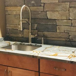 Idéer för en mellanstor modern blå linjär tvättstuga enbart för tvätt, med en undermonterad diskho, skåp i shakerstil, skåp i mellenmörkt trä, granitbänkskiva, bruna väggar och en tvättmaskin och torktumlare bredvid varandra