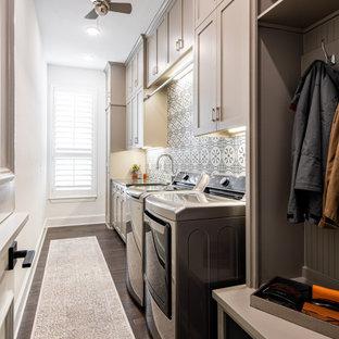 Esempio di una lavanderia multiuso classica di medie dimensioni con lavello stile country, ante in stile shaker, ante grigie, pareti bianche, pavimento in legno massello medio, lavatrice e asciugatrice affiancate, pavimento marrone e top nero