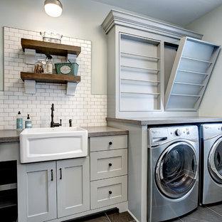 Klassische Waschküche in L-Form mit Landhausspüle, Schrankfronten im Shaker-Stil, grauen Schränken, grauer Wandfarbe, Waschmaschine und Trockner nebeneinander, grauem Boden und grauer Arbeitsplatte in Grand Rapids