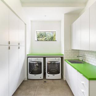 Свежая идея для дизайна: отдельная, п-образная прачечная в современном стиле с зеленой столешницей, плоскими фасадами, белыми фасадами, белыми стенами, бетонным полом, со стиральной и сушильной машиной рядом, серым полом, врезной раковиной и столешницей из ламината - отличное фото интерьера