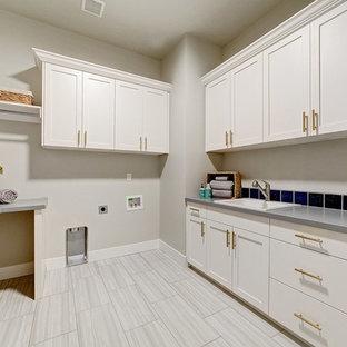 Immagine di una sala lavanderia american style di medie dimensioni con lavello da incasso, ante con riquadro incassato, ante bianche, top in quarzo composito, pareti grigie, pavimento in gres porcellanato, lavatrice e asciugatrice affiancate, pavimento grigio e top grigio