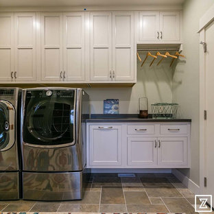 Photo of a mid-sized arts and crafts single-wall dedicated laundry room in Other with shaker cabinets, white cabinets, white walls, slate floors and a side-by-side washer and dryer.