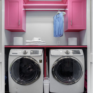 Inspiration for a small transitional single-wall laundry cupboard in Philadelphia with recessed-panel cabinets, solid surface benchtops, laminate floors, black floor and grey walls.