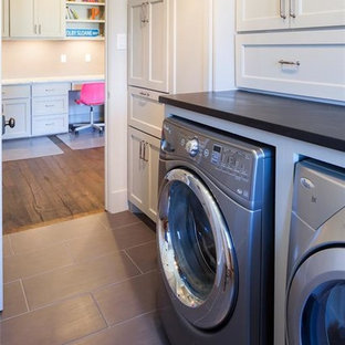 Large contemporary l-shaped utility room in Houston with shaker cabinets, white cabinets, grey walls, granite worktops, a side by side washer and dryer, black worktops, a submerged sink, slate flooring and grey floors.