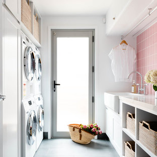 Photo of a mid-sized beach style galley dedicated laundry room in Brisbane with a farmhouse sink, open cabinets, white cabinets, a stacked washer and dryer, grey floor, white walls and white benchtop.