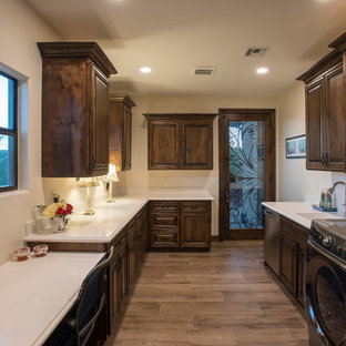 This is an example of a large country u-shaped utility room in Phoenix with an undermount sink, raised-panel cabinets, dark wood cabinets, quartz benchtops, beige walls, medium hardwood floors, a side-by-side washer and dryer, brown floor and turquoise benchtop.