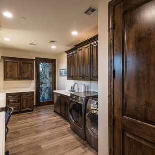 Large country u-shaped medium tone wood floor and brown floor utility room photo in Phoenix with an undermount sink, raised-panel cabinets, dark wood cabinets, quartz countertops, beige walls, a side-by-side washer/dryer and turquoise countertops