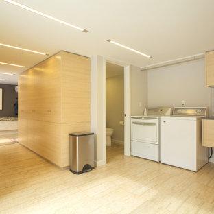 Idéer för mycket stora funkis l-formade grovkök, med en undermonterad diskho, släta luckor, skåp i ljust trä, beige väggar, bambugolv och en tvättmaskin och torktumlare bredvid varandra